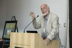 At lectern giving a lecture.