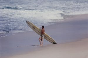 Noll at the beach, holding surfboard.
