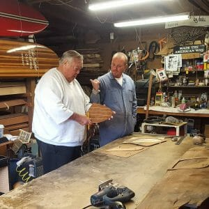 Noll and younger man at workbench.